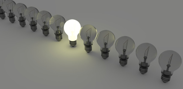 An image of lightbulbs in a row with one switched on